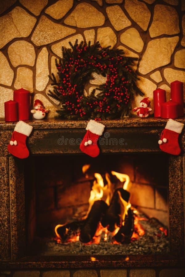 Aqueça a chaminé acolhedor decorada para o Natal com o burni de madeira real imagem de stock