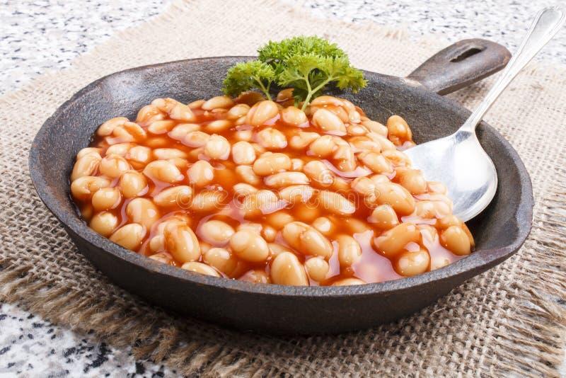 Aqueça feijões cozidos no molho de tomate servido em uma bandeja do ferro fundido imagens de stock royalty free