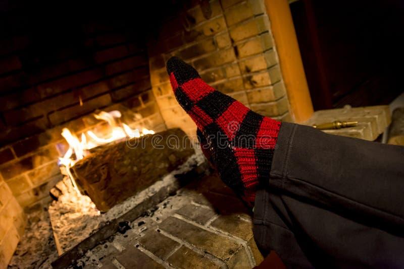 Aquecendo seus pés em uma chaminé fotografia de stock royalty free