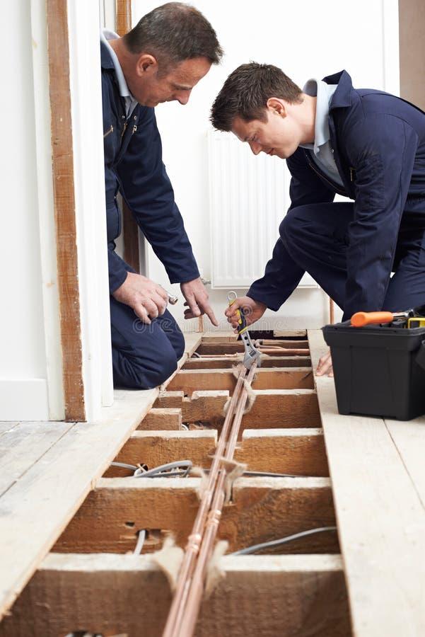 Aquecimento central de And Apprentice Fitting do encanador na casa foto de stock