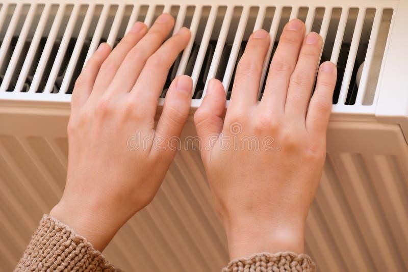 Aquecimento das mãos com radiador de aquecimento imagem de stock