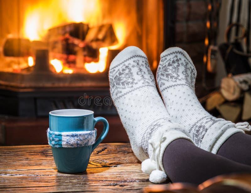 Aquecimento e relaxamento perto da chaminé com um copo da bebida quente foto de stock royalty free