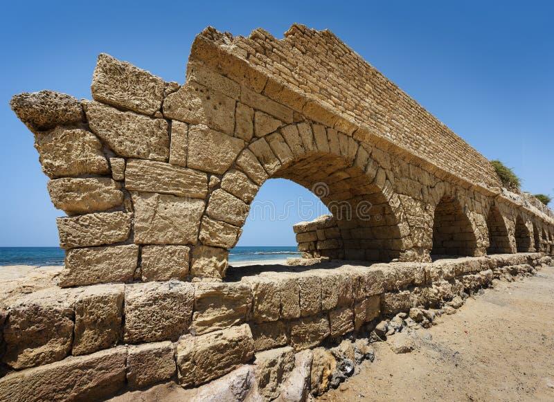 Aqueduto romano antigo em Ceasarea na costa do Mediterra imagens de stock royalty free