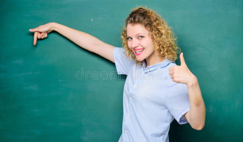 Aqui est? Educa??o Vida dos estudantes professor da mulher na lição da escola Dia do conhecimento informação vazia do quadro-negr imagem de stock royalty free
