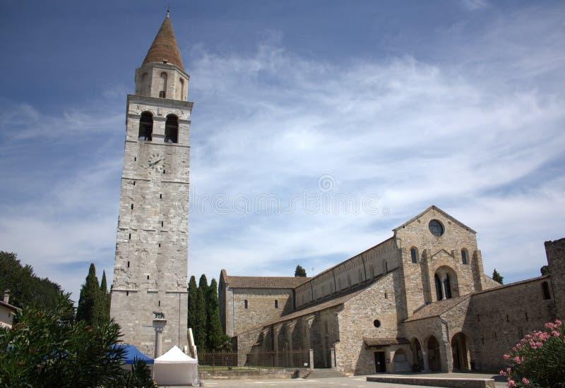 Aquileia - den Santa Maria Assunta domkyrkan och sätta en klocka på står hög arkivbild