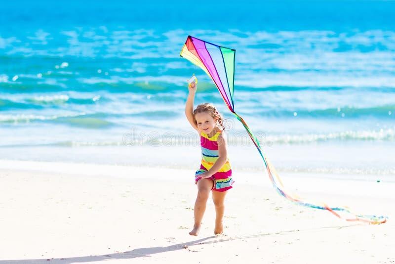 Aquilone di volo del bambino sulla spiaggia tropicale fotografia stock
