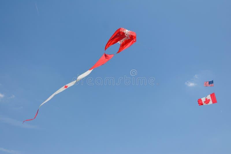Aquiloni canadesi variopinti che pilotano gli aquiloni variopinti degli aquiloni dei cieli blu immagine stock