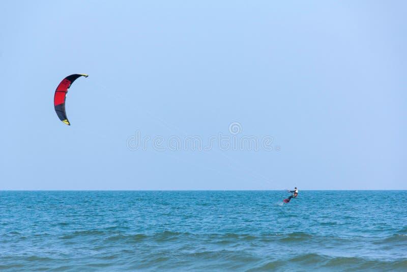 Aquiloni di un uomo che praticano il surfing al mare in Tailandia e ad un cielo blu nei precedenti fotografie stock