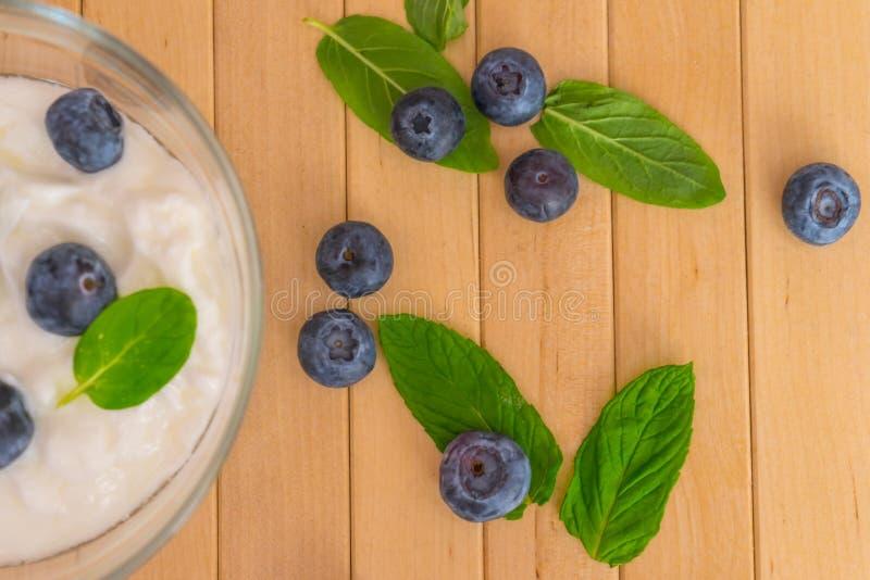 Arándanos con las hojas del yogur y de la menta en la tabla de madera imagenes de archivo
