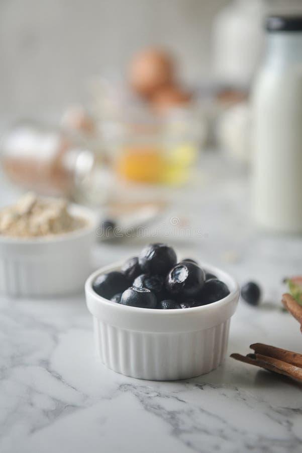 Arándanos frescos en cuenco, en la tabla de mármol El concepto de cocinar los ingredientes, adorna la panadería, consumición sana imagen de archivo