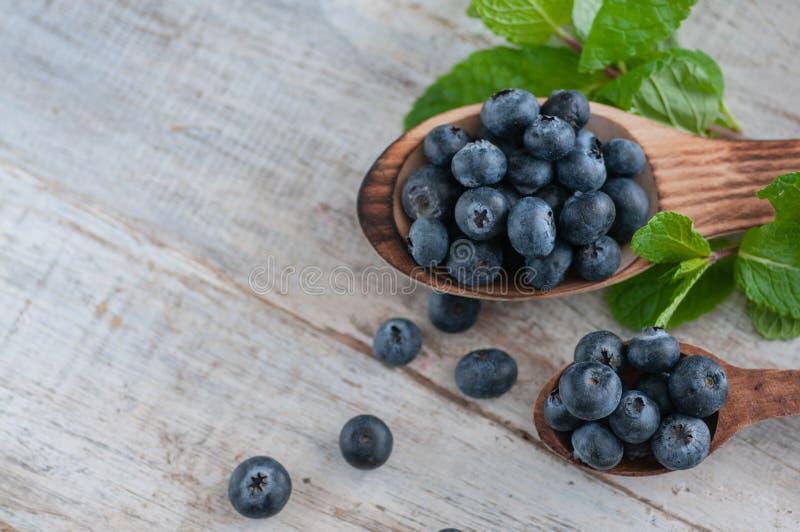 Arándanos y diversas frutas del bosque, frambuesas, fresas Hay diversos tipos de madera en la tabla imagen de archivo