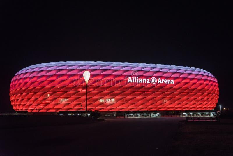 Arène d'Allianz, le stade de football de FC Bavière, illuminé en rouge avec le blanc sur le dessus la nuit photos libres de droits