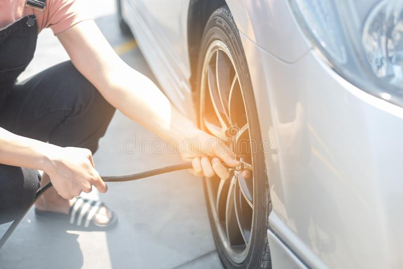 Ar de enchimento da mulher asi?tica em um pneu de carro para aumentar o pneu de carro da press?o fotografia de stock