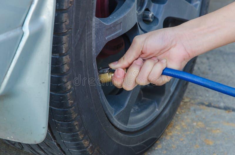 Ar de enchimento em um pneu de carro fotos de stock