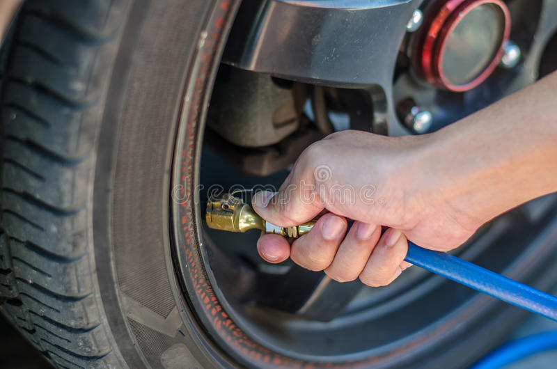 Ar de enchimento em um pneu de carro imagens de stock