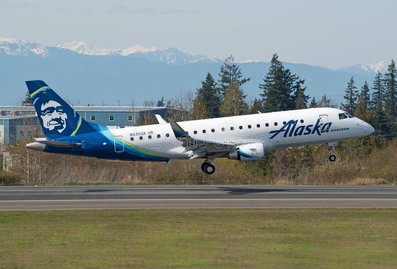 Ar do horizonte de Embraer ERJ-175 Alaska aproximadamente à aterrissagem na pista de decolagem foto de stock