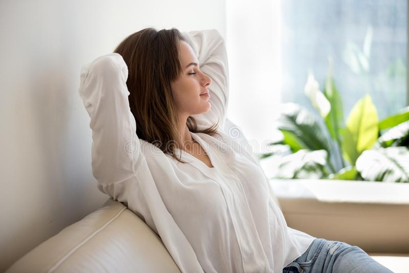 Ar fresco de respiração de descanso da mulher relaxado em casa no sofá fotografia de stock royalty free