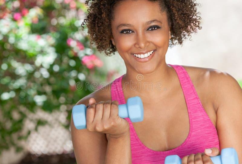 Ar livre afro-americano da mulher que exercita com pesos fotografia de stock
