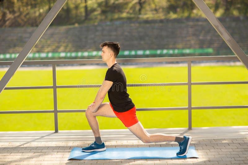 Ar livre da ioga do treinamento do homem novo O indiv?duo desportivo faz o estic?o do exerc?cio em uma esteira azul da ioga, na t imagens de stock