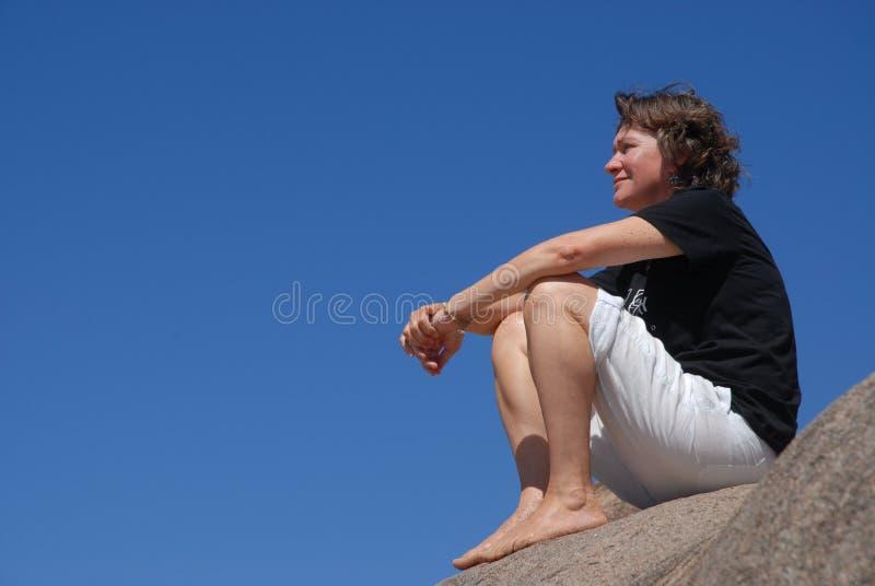 Ar livre da mulher, sentando-se em uma rocha no verão imagens de stock