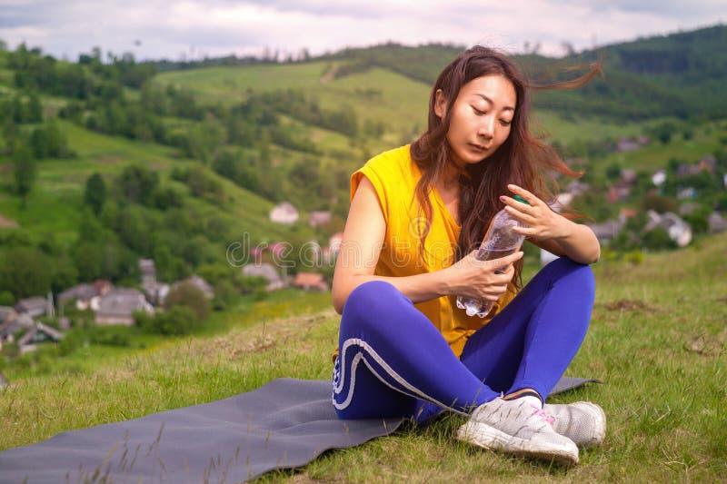 Ar livre de relaxamento e água potável da mulher bonita nova do esporte após o esporte imagem de stock royalty free