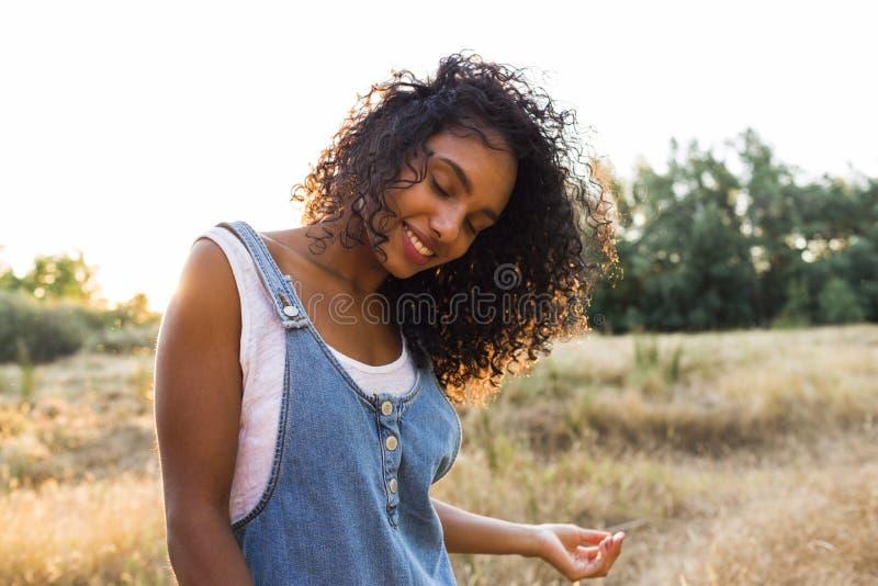 Ar livre do retrato de um smili afro-americano novo bonito da mulher imagem de stock