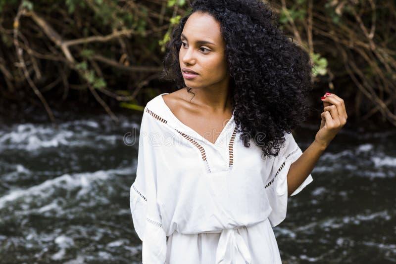 Ar livre do retrato de uma mulher afro-americana nova bonita na SU imagens de stock royalty free