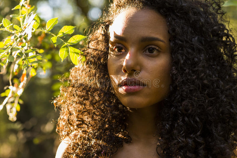 Ar livre do retrato de uma mulher afro-americana nova bonita na SU imagem de stock royalty free