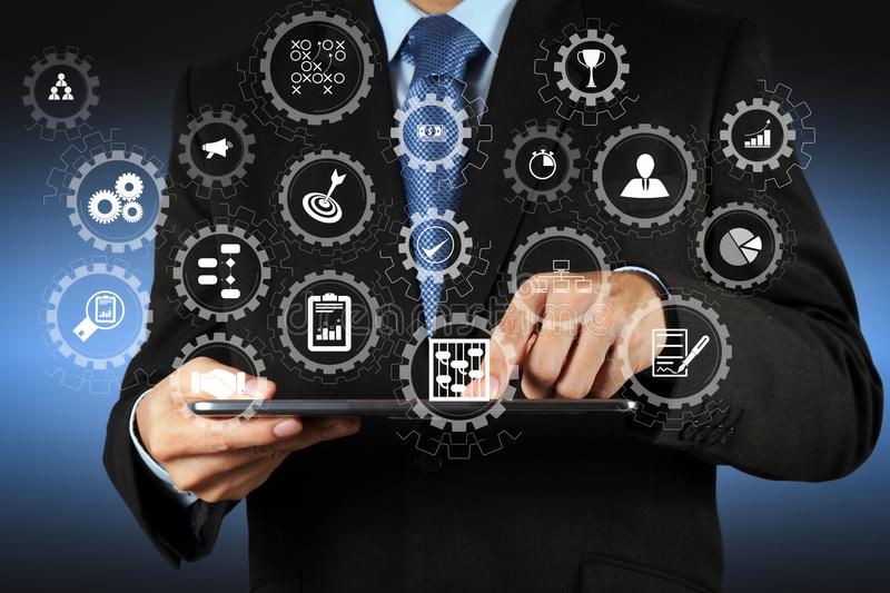 Businessman using tablet computer. AR virtual screen dashboard with project management with icons of scheduling, budgeting, communication.businessman hand using royalty free stock photography