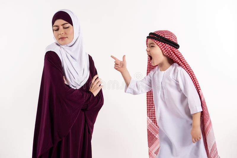 Arab boy is arguing with mother in hijab. royalty free stock image