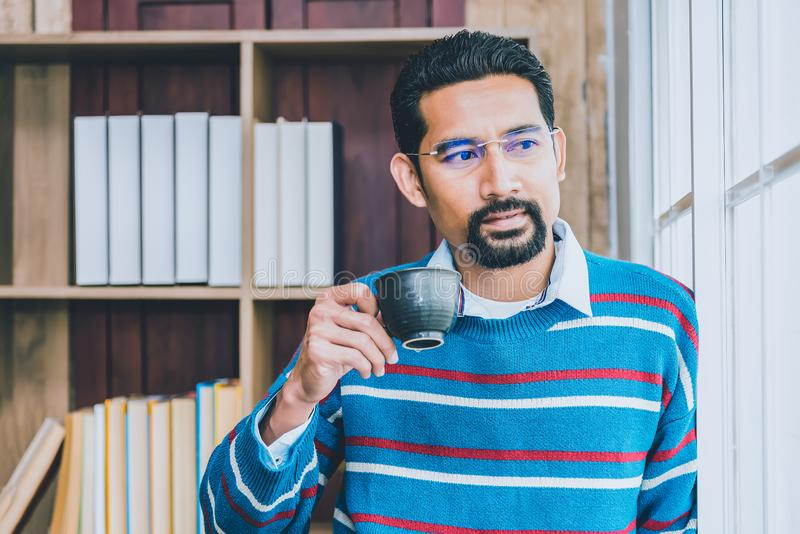 Arab businesman in casual clothes taking a break from work, standing near the window holding cup of coffee blurred black ground of stock photo