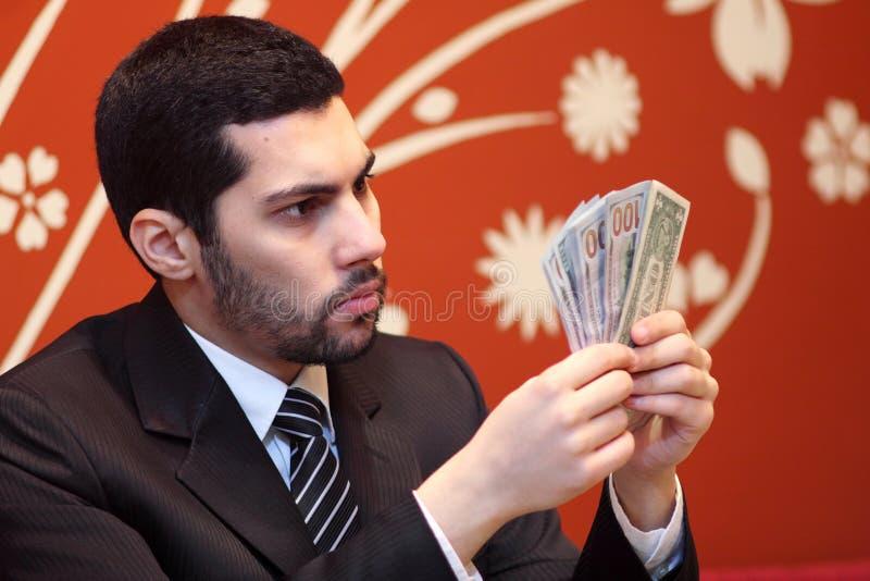 Arab business man with dollar bills. Arab business man wearing black suit and looking at dollar bills stock photo