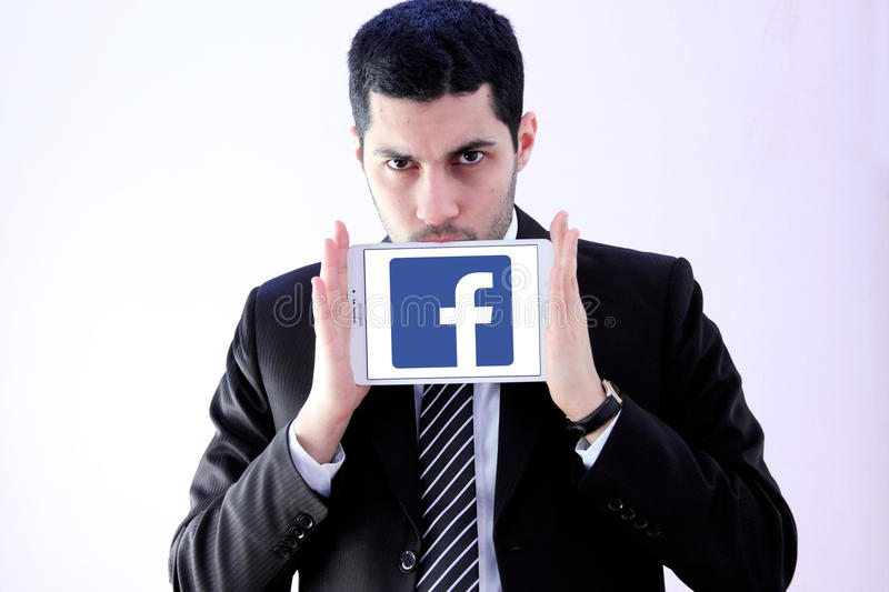 Arab business man with facebook logo. Photo of arab business man wearing black suit and holding white tablet with facebook on display royalty free stock images