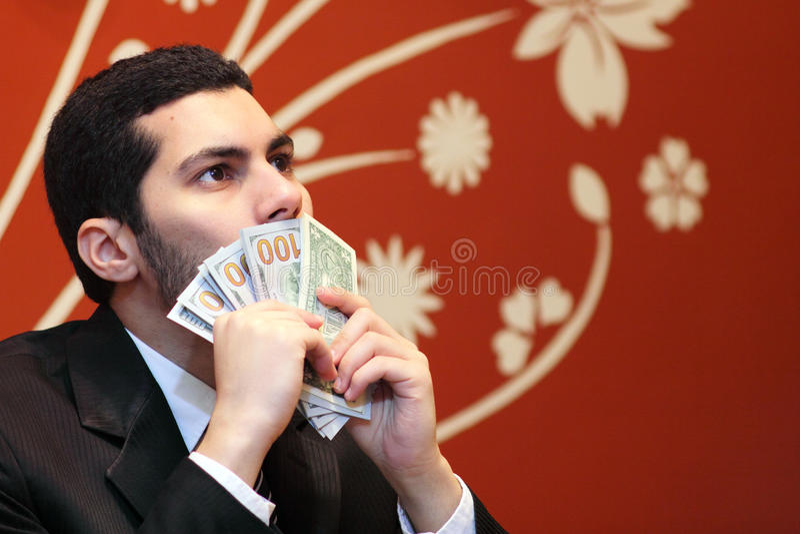 Arab business man kissing dollar bills. Arab business man wearing black suit and kissing dollar bills royalty free stock images