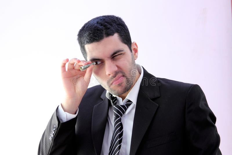 Arab business man looking through money. Image of arab business man wearing black suit and looking through money royalty free stock photo