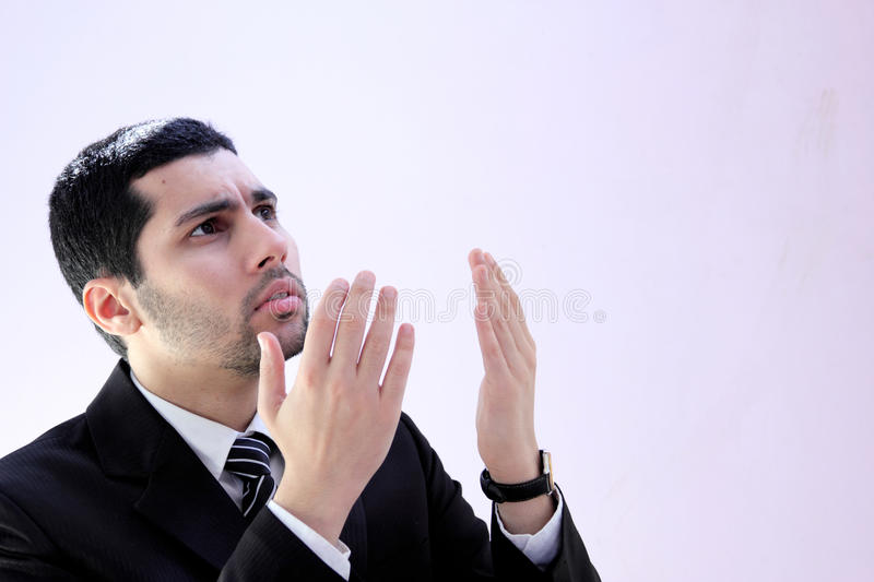 Arab business man praying for help. Image of arab business man wearing black suit and raising his hands asking god for help royalty free stock photo