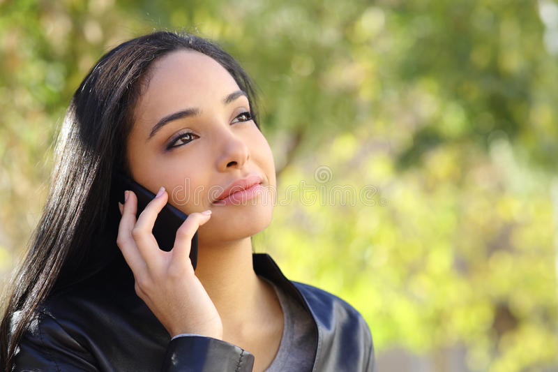Arab business woman on the mobile phone in a park. With a green background stock image