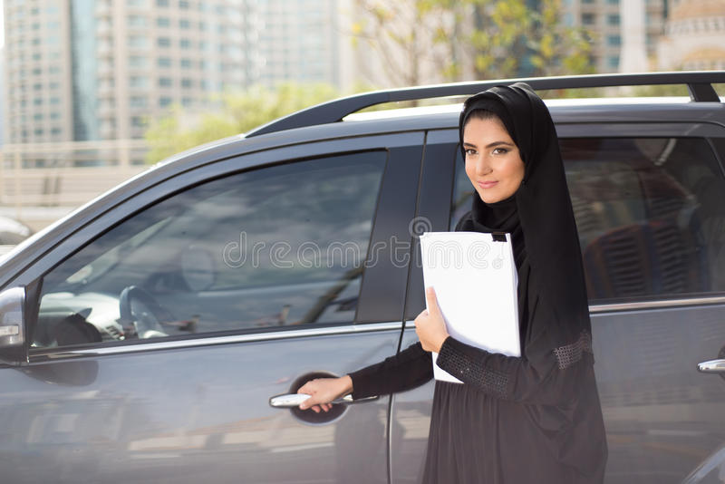 Arab Business Woman Standing next to a Car. Arab Business Woman with Documents Standing next to a Car stock photos