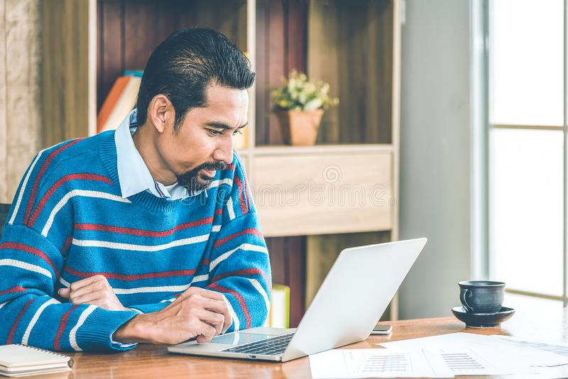 Arab businessman in casual clothes  working in the office with laptop, paper, note and a cup of coffee on working table stock image