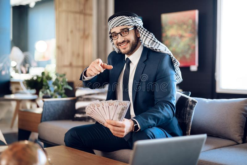 Arab businessman counting money on couch at hotel room. royalty free stock photo