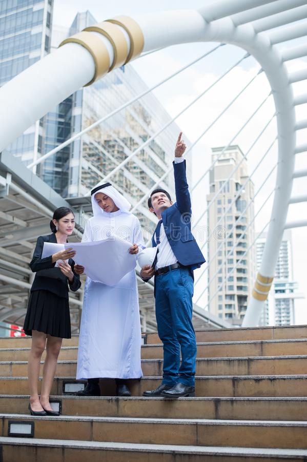 Arab businessman holding blueprint on hand and talk about construction process with Asian businessman and businesswoman royalty free stock photo