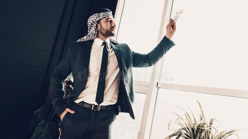 Serious Arab played by an airplane model royalty free stock photos