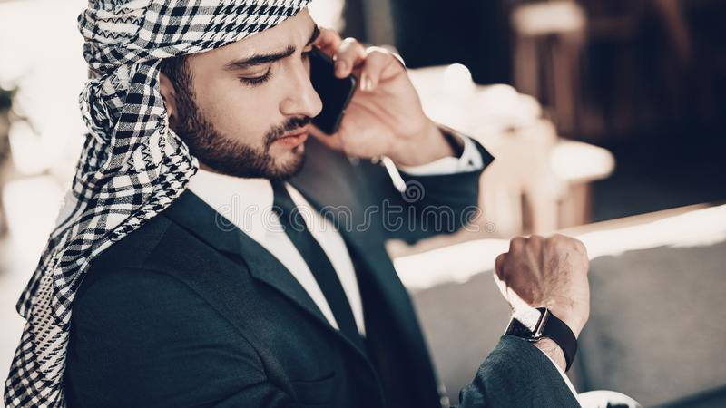 Close up photo of Arab looking at wristwatches royalty free stock photography
