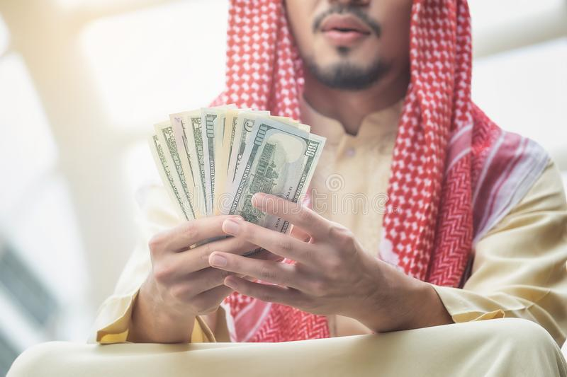 Arab businessmen see dollars with satisfaction in business profits. Focus on the dollar stock image