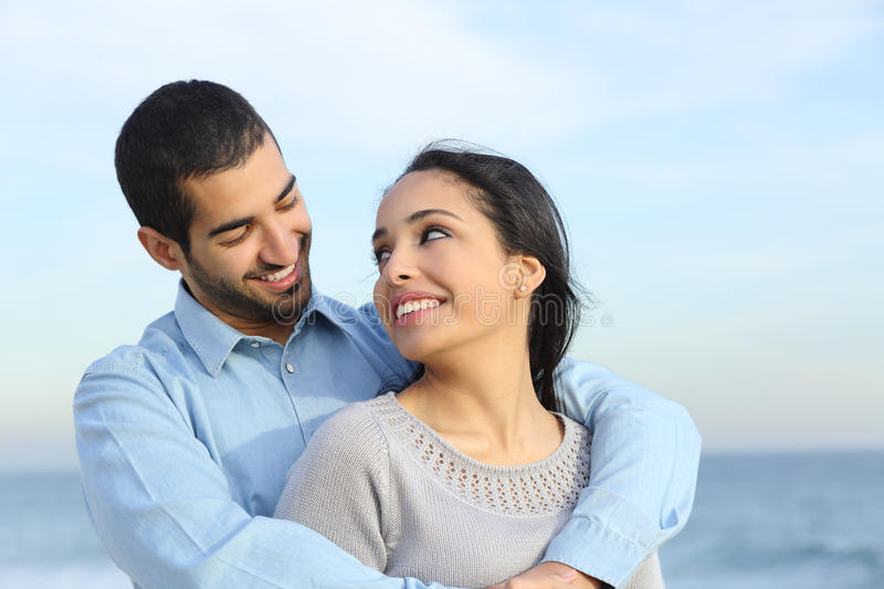 Arab casual couple cuddling happy with love on the beach. With the horizon and the sea in the background stock photo