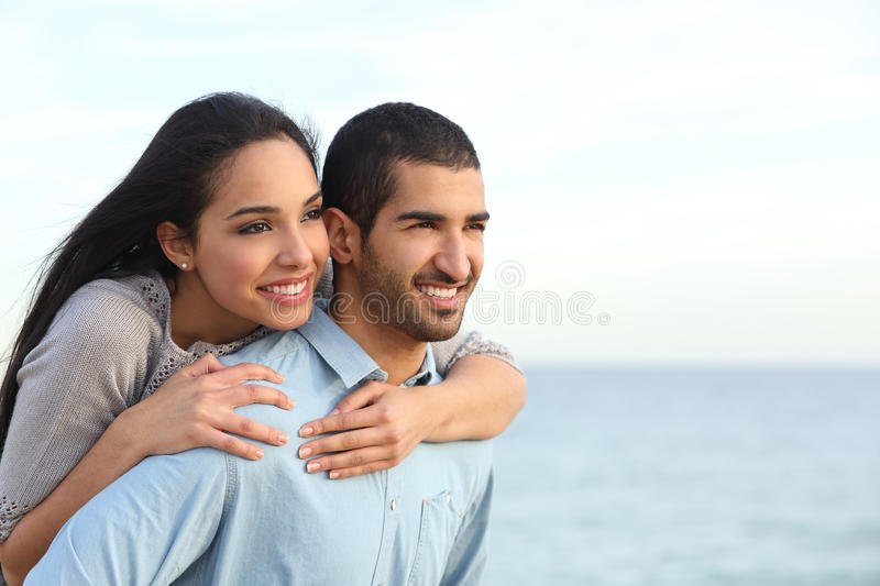 Arab couple flirting in love on the beach. Arab couple flirting piggyback in love on the beach with the sea in the background