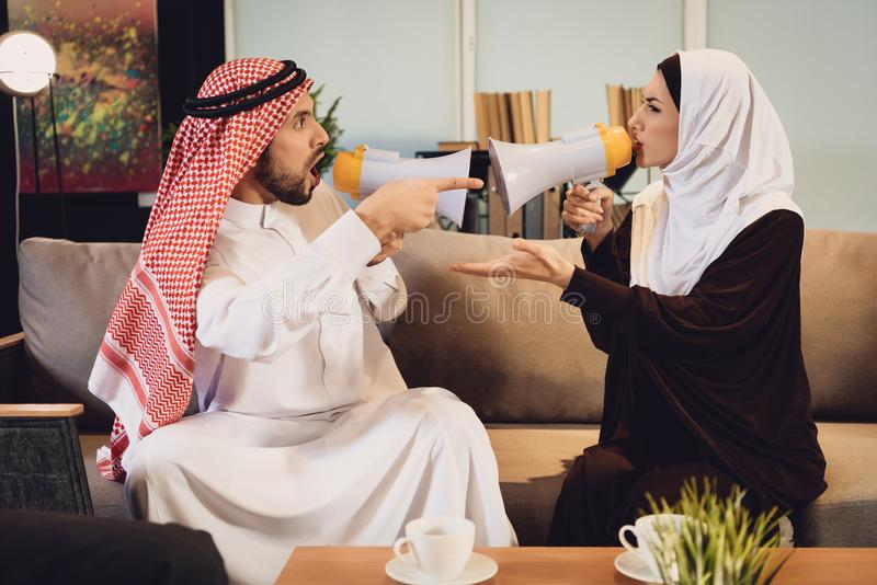 Arab couple screaming at each other in megaphone stock photo