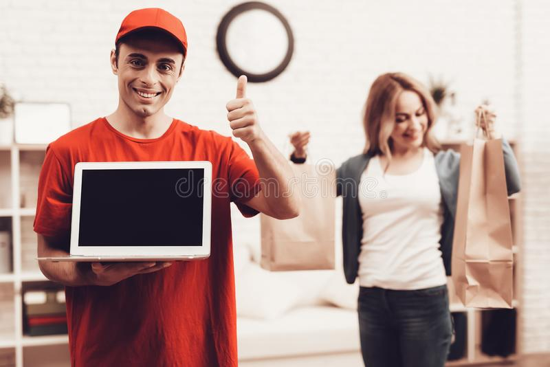 Arab Deliveryman with Laptop and Girl with Packege. Courier Delivery. Man Deliveryman with Laptop. Worker Man Arab Nationality. White Interior. Deliveryman Arab stock photos
