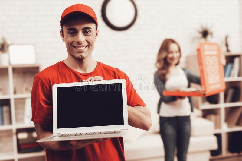 Arab Deliveryman with Laptop and Girl with Pizza. Courier Delivery. Man Deliveryman with Laptop. Worker Man Arab Nationality. White Interior. Deliveryman Arab royalty free stock photos