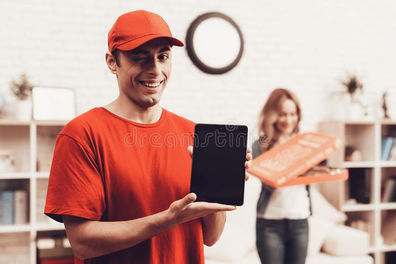 Arab Deliveryman with Tablet and Girl with Pizza. Courier Delivery. Man Deliveryman with Tablet. Worker Man Arab Nationality. White Interior. Deliveryman Arab stock photos
